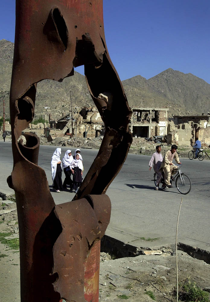 School children and pedestrians walk through the bombed out district of Kart-e-seh in Kabul, Afghanistan.
