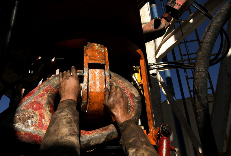 With his hands covered in grease and grit, worker, Shawn Howard, changes out a piece of equipment on a Bronco Drilling rig located near the Roan Plateau in Rio Blanco County Tuesday 11/20/07.  Photo by Matt McClain
