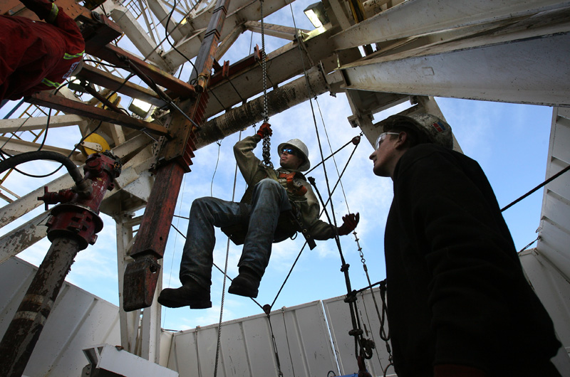 Greg Hall, right, watches as driller, Cody Hollenbach is hoisted into the air to unhook equipment as maintenance work is done to a Bronco Drilling rig Tuesday 11/20/07 near the Roan Plateau in Rio Blanco County.  Photo by Matt McClain
