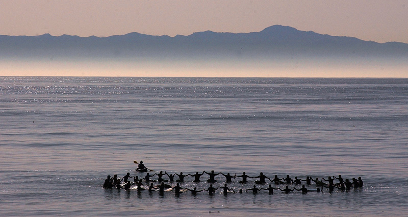 Surfers form a circle during a paddle out in honor of the ten victims of the La Conchita mudslide on the one year anniversary.  Photo by Matt McClain