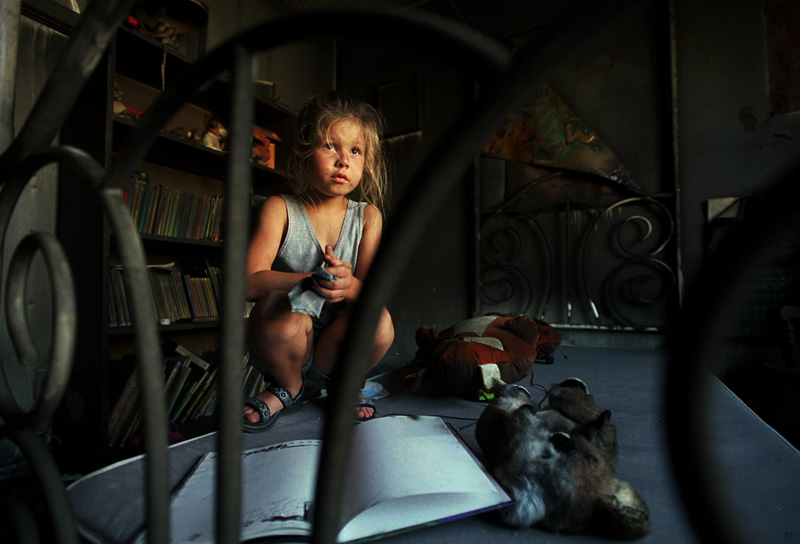 Myste Wood, 7, sits on the bed in her fire damaged room as her mother, Patty Wood tries to salvage belongings and list damaged items for insurance purposes.  The Wood's Oxnard condo was destroyed by a fire.  Photo by Matt McClain
