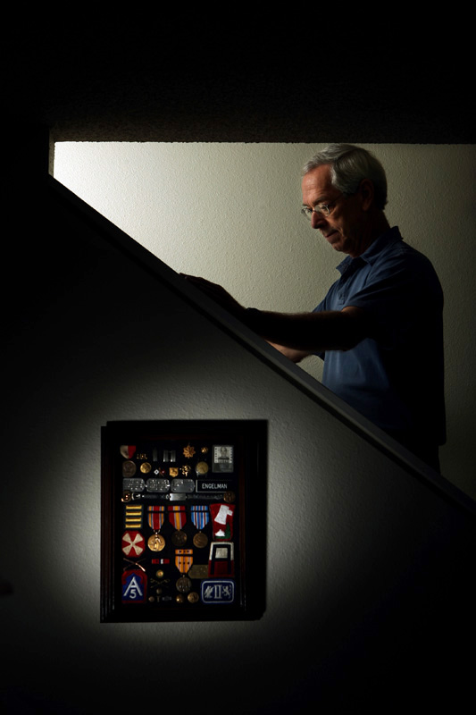 Ted Engelmann stands next to a display of his father's World War II medals.  Ted's father, George Engelmann Jr. taught him photography and also was influential in his military career.  Photo by Matt McClain