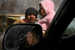 Deanna Ramirez, seen in her vehicle's side view mirror, is pictured with husband, Julio Ramirez, and their daughter, Alexandria Ramirez, 4, as they talk Thursday outside their Pueblo trailer home about  Nicole Uribe-Lopez, who is charged with trying to sell her five month old son, Jason Hines to Jose-Juan Lerma and his wife, Irene Lerma.  Photo by Matt McClain