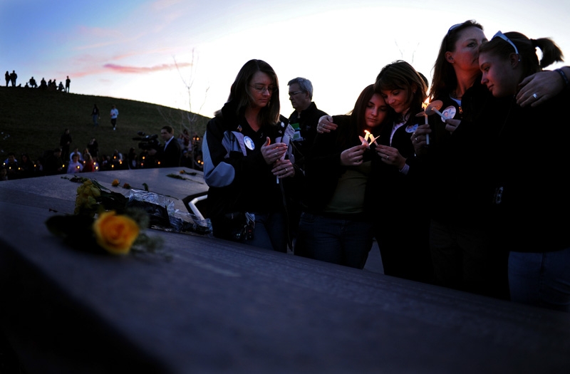 Relatives of slain Columbine High School teacher, David Sanders, granddaughter Mallory Sanders, 17, center, is embraced by mother, Coni Sanders, as her sister, Cindy Thirouin, second from right, kisses her daughter, Tiffany Strole, 15, during a candlelight vigil at the Columbine Memorial at Clement Park in Littleton, Colo. Sunday 04/19/09 in honor of the tenth anniversary of the school shooting which is Monday. (PHOTO BY MATT MCCLAIN)