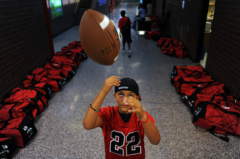 Rangeview High School ball boy and son of head coach Dave Gonzales, Max Gonzales, 10, plays with a football in the hallway as the players bags can be seen lining the walls before the team played Gateway High School  Friday 09/11/09 at Aurora Public School Stadium.  Photo by Matt McClain