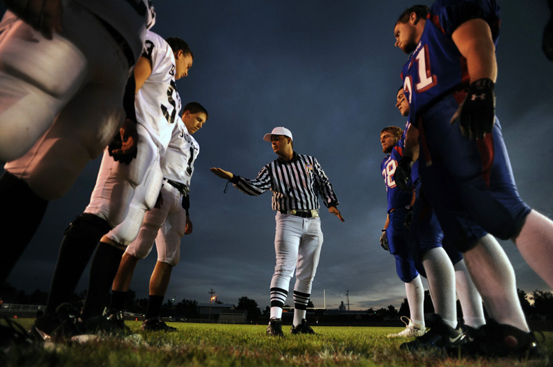 Head referee, Frank Phillips shows the winning toss of the coin to Limon High School football captains, left, and members of Akron High School on Friday 09/25/09 in Akron, Colo. Photo by Matt McClain