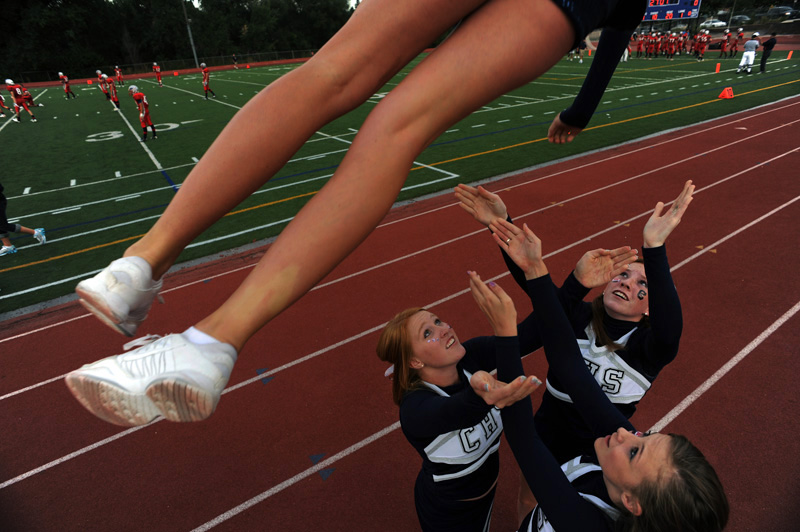 Columbine High School cheerleaders, Kayla Northrup, center, Ashton Everly, bottom, and Annie McNally, right, catch fellow cheerleader, Olivia Kroonenberd,top, after performing a liberty stunt prior to a football game between Columbine High and Heritage High School Friday 09/05/09 at Littleton Public Schools District Stadium in Littleton, Colo.  Photo by Matt McClain