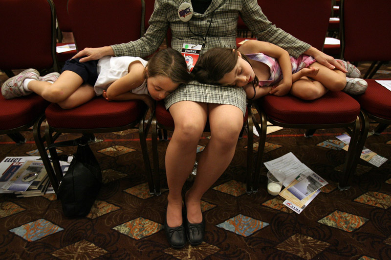 Republican State Convention Delegate, Stacy Button listens to the proceedings as her twin daughters, Haley Button, 7, left, and Hannah Button, 7, right, sleep on her lap at the Grand Sierra Resort in Reno, Nev.  Photo by Matt McClain