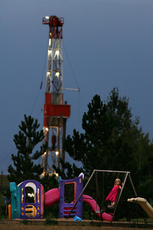 As a gas drilling rig begins to light up the evening sky, Katrina West, 5, plays on a swing set in the backyard of her grandparents Oxford Farms home of outside Erie, Colo.  Photo by Matt McClain