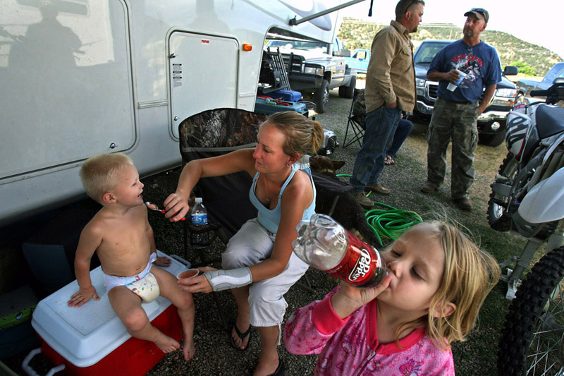 Frances Hoffpowier, center left, feeds her youngest son, Mason, 2, as her daughter Chloe, 4, takes a drink of soda while the families' father, Michael Hoffpowier, talks with fellow natural gas worker, Tommy Jones at the River Camp RV Park outside of Meeker, Colo.  The family moved from Texas so Michael could make better money as a welder in the gas fields.  Gas workers see a conflict between themselves and locals in the community they now call home.  {quote}The people here have absolutely no use for us,{quote} Hoffpowier said.  Photo by Matt McClain