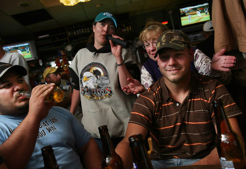 Blowing off steam after a twelve hour day of work, atural gas roughneck workers, Joe Rodriguez of Cheyenne, Wyoming, left, and Kamron McMahan of St. Jo, Texas, right, are sung a karoke song by Tawnia Marney, back left, and Debbie Gieck , back right, at the Sports Corner Saloon in downtown Rifle, Colo.  Photo by Matt McClain