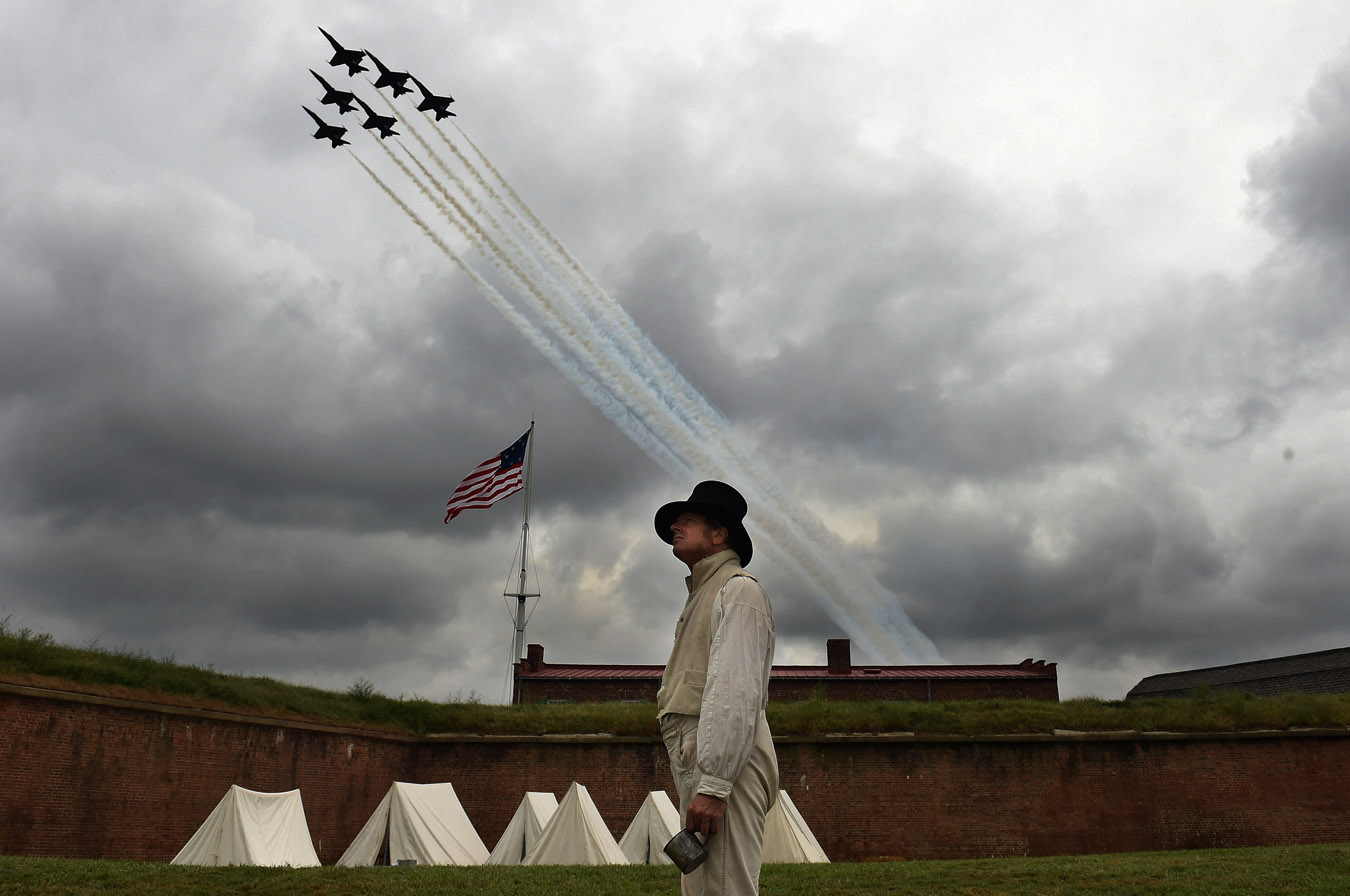 Reenactor, Gary Schwartz of Silver Spring, MD stands near an encampment as the Blue Angels fly overhead during the Star-Spangled Spectacular Air Show which was part of the festivities celebrating the 200th anniversary of the penning of {quote}The Star-Spangled Banner{quote} and the Battle of Baltimore at Fort McHenry National Monument and Historic Shrine on Saturday September 13, 2014 in Baltimore, MD.  (Photo by Matt McClain/ The Washington Post)
