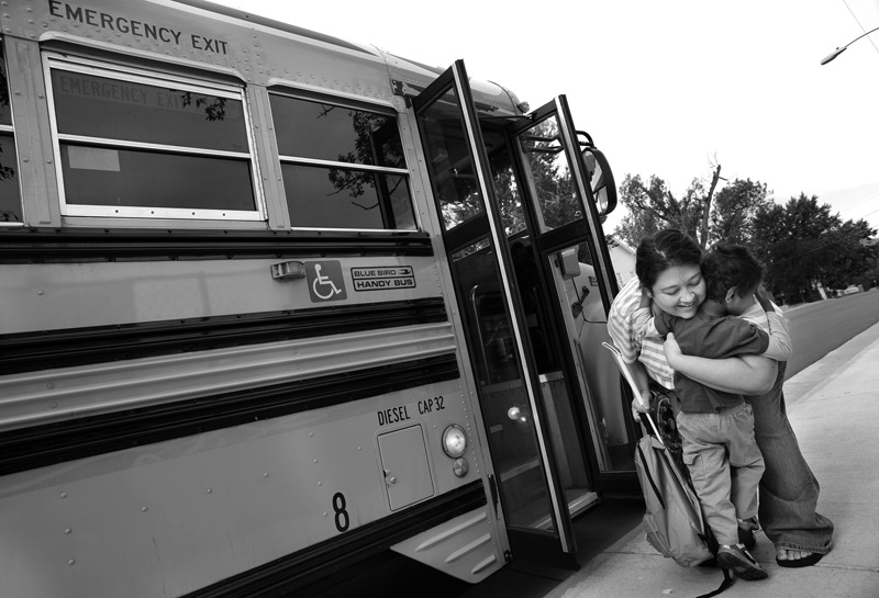 Lalena Fayre hugs her son, Pandu Fayre after he rode the school bus Tuesday 06/16/09 for the first time from their Englewood home to the Village Pathways in Littleton, Colo.