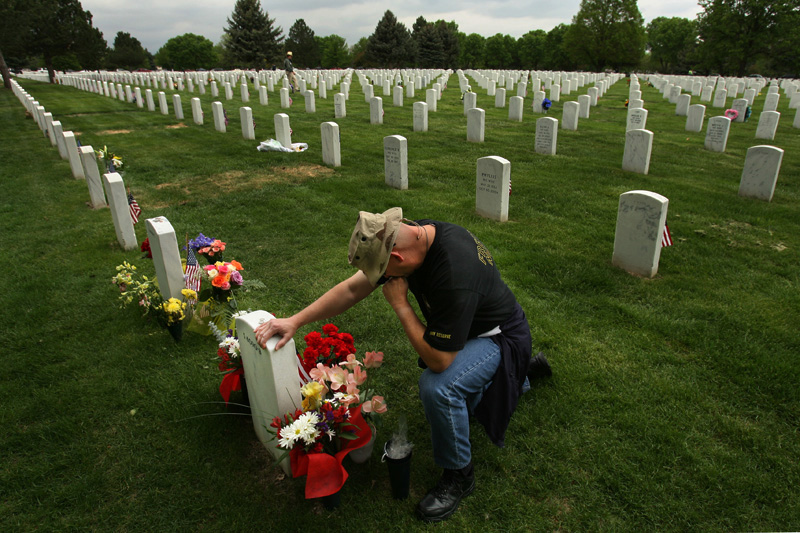 Lt. Col. Robert Thompson kneels and cries in Fort Logan National Cemetery in Denver, Colo. next to the grave of Master Srgt. Robert West, who he served with in Iraq.  Thompson was with West when he was killed by an IED south of Baghdad in 2006.  Photo by Matt McClain