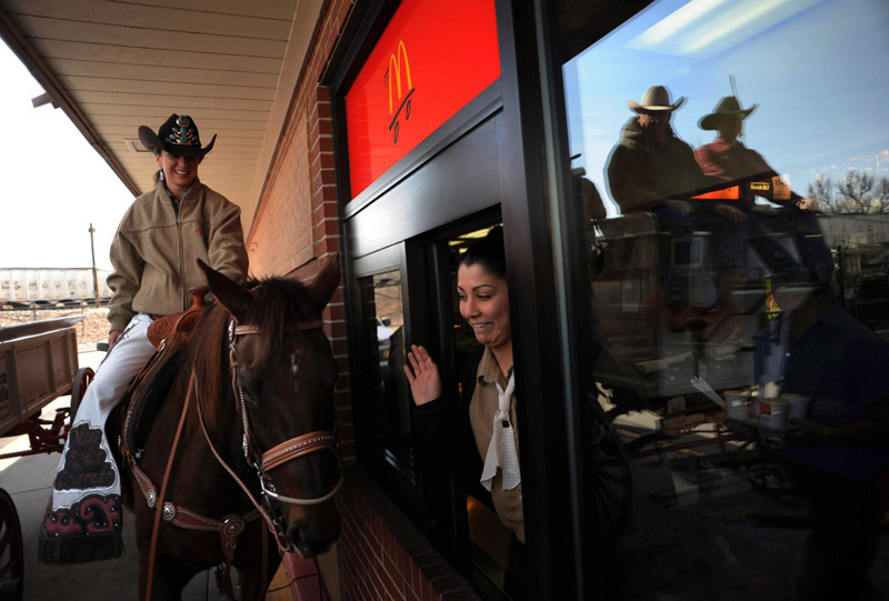 Miss Rodeo Colorado, Audra Dobbs, left, sits on her horse, Sequoia as she suprises Lizeth Saemz at a McDonalds drive thru window  as participants of the Rocky Mountain Horse Expo got in the drive thru line to get shakes after putting on a display for students at Garden Place Academy in Denver, Colo.  Photo by Matt McClain