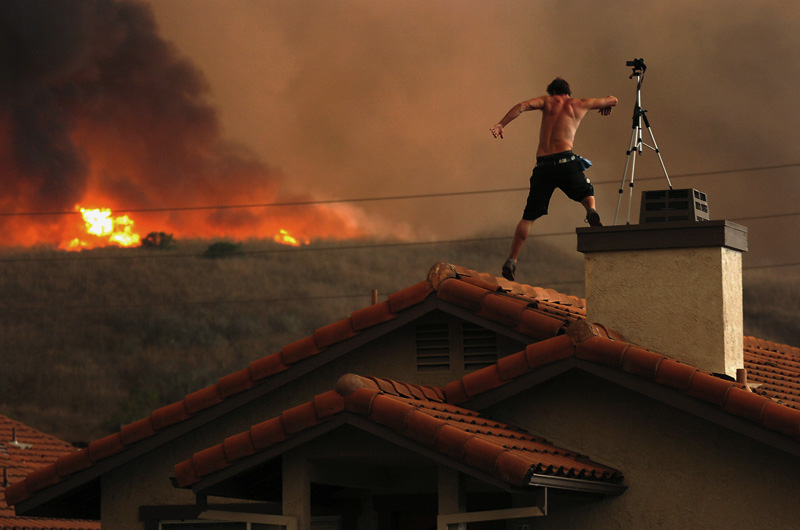 Nathan Graham video tapes an approaching brush fire on top of the Las Virgenes Townhouses in Calabasas, Calif.  Photo by Matt McClain