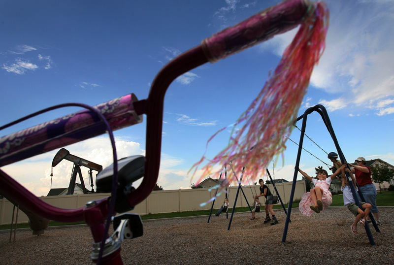 Gabrielle Van Winkle, 8, plays on a swing as an oil derrick is seen in the background of park equipment in the Summit View neighborhood of Fredrick Colo.  Photo by Matt McClain