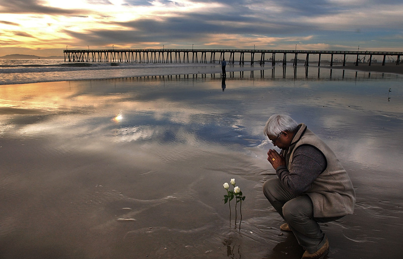 Binod Prasad prays after placing three flowers in the sand in memory of his son, Anjesh Prasad and nephews, Avinash Prasad and Amit Deo during the sixth anniversary of the fatal crash of Alaska Flight 261 in Port Hueneme, Calif.  Photo by Matt McClain