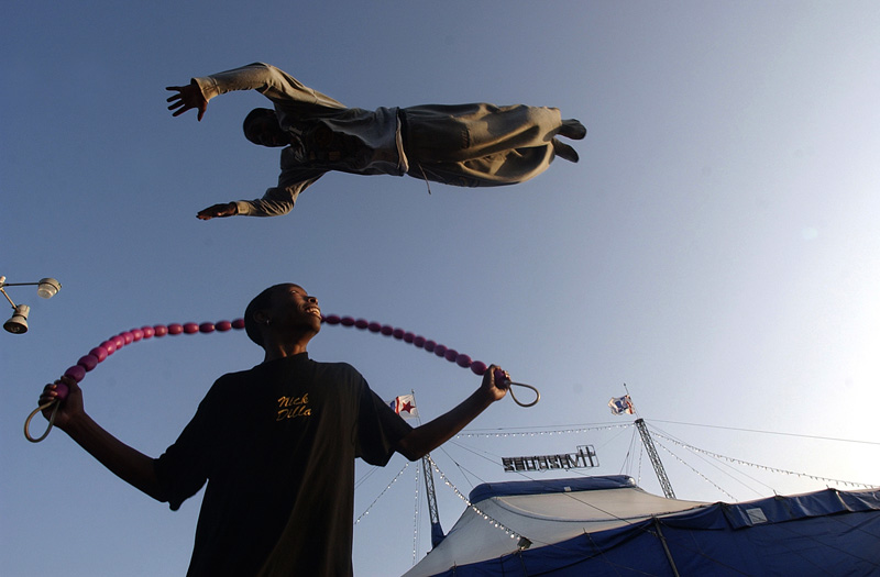 Practicing before the first performance of the evening for Circus H. Vazquez, Nick Hegwood, 16, jumps a rope as Montie Bledsoe, 20, uses a trampoline to sky over him at Seaside Park in Ventura, Calif.  Photo by Matt McClain