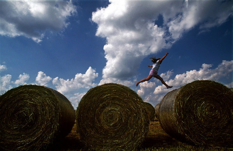 Leaping from hay bales, Erin Mencher, 9, plays in a field near her family's Bloomington, Ind. home on a fall afternoon.  Photo by Matt McClain