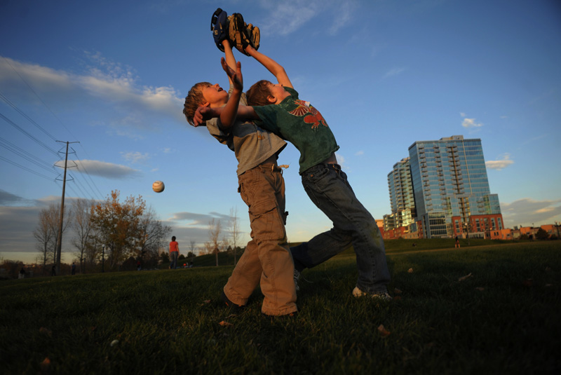 Eli Dunn, 7, left, competes for a fly ball with Dylan Carey, 8, right, as Dylan's father, Marc Carey throws pop ups to them in an open space near the Platte River in Denver, Colo. on Saturday 11/07/09.  Photo by Matt McClain