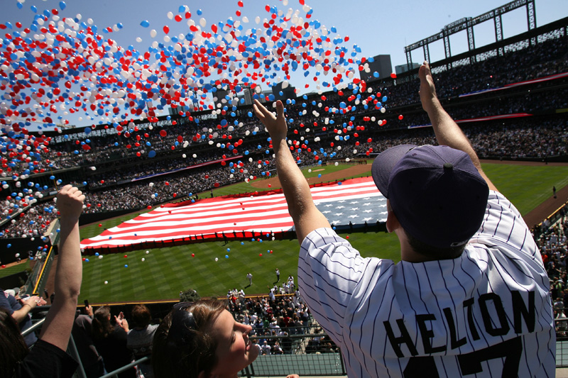 Alyssa Alcorta, 19, center bottom, looks up to friend, Andrew Baker, 21, as he stretches his arms out to balloons being released during the opening ceremonies before the Colorado Rockies first home game of the season with the Arizona Diamondbacks at Coors Field in downtown Denver.  Photo by Matt McClain