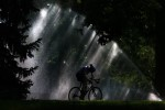 As the rising sun streaks behind a sprinkler, a bicyclist gets in an early morning ride before the heat of another afternoon in the mid-90 degrees sets in at Washington Park in Denver, Colo. Photo by Matt McClain
