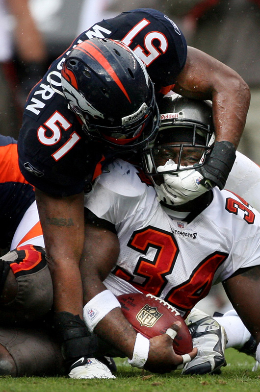 Jamie Winborn, top, of the  Denver Broncos pulls the helmet of Earnest Graham of the Tampa Bay Buccaneers after tackling him in the fourth quarter at Invesco Field at Mile High in Denver. Photo by Matt McClain