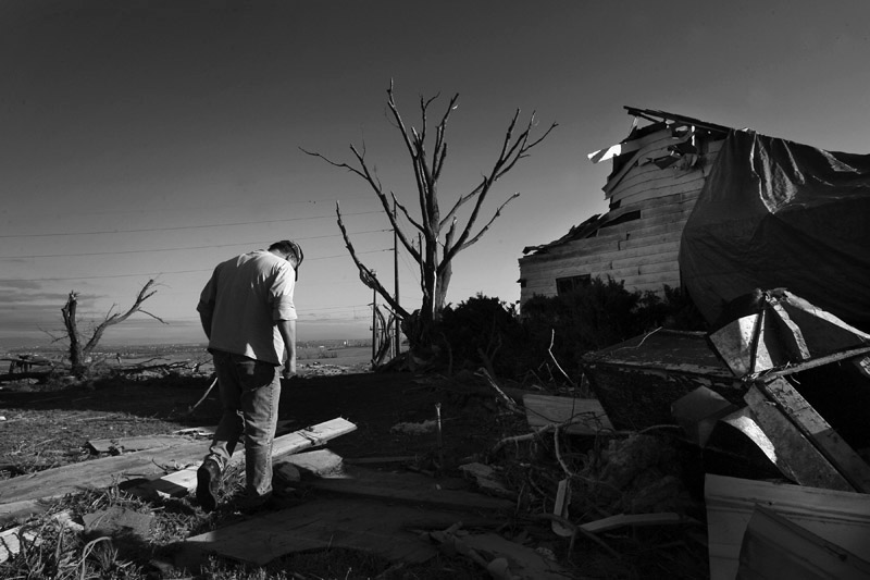 Chuck Gully walks around his home, a day  after a large tornado destroyed it and other homes in Windsor, Colo.  Photo by Matt McClain