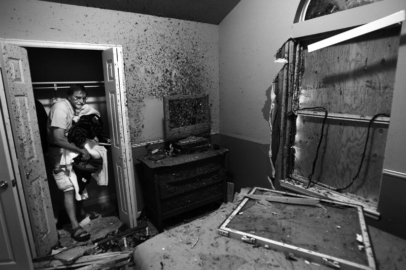 Kenny Coffman throws away damaged items from his and his roommate's home in Windsor, Colo.  Photo by Matt McClain