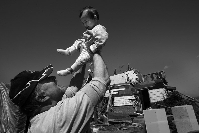 Chuck Gully holds up his youngest daughter, Erika Gully, 11 months, outside their home on the outskirts of Windsor, Colo.  Gully was reunited with his family after being out of town when the tornado struck.  Photo by Matt McClain