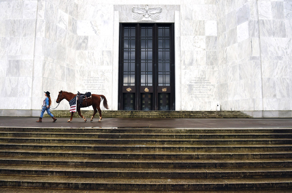 A demonstrator walks with a horse as she prepares to take part in a rally outside the Oregon State Capitol to honor LaVoy Finicum, who was killed by law enforcement officers and the men who were arrested in connection to the occupation of the Malheur National Wildlife Refuge on Saturday March 05, 2016 in Salem, OR. (Photo by Matt McClain/ The Washington Post)