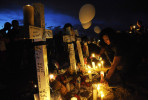 Rachel Fogleman, 13, of Aurora, CO lights candles near a makeshift memorial that includes twelve crosses across the street from the Century Aurora 16 movie theater on Sunday July 22, 2012 in Aurora, CO.  The crosses represent the twelve people who were killed in a deadly shooting Friday morning at the movie theater.