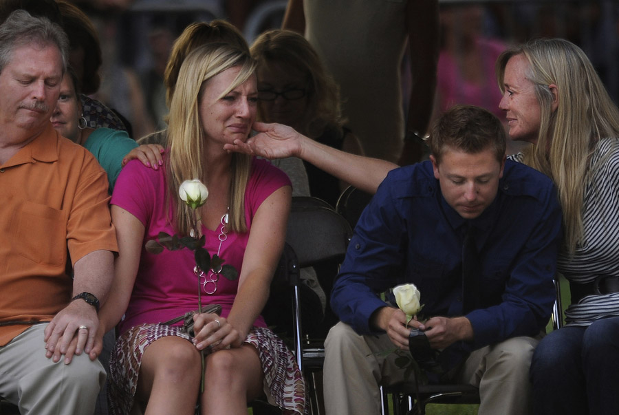 Amanda Lindgren, left, is consoled during a community vigil for those killed and injured at the Century Aurora 16 movie theater shooting on Sunday July 22, 2012 in Aurora, CO.  Lindgren's boyfriend, Alexander Teves died while protecting her during the shooting.  The event was to honor the memories of those injured and killed in the deadly shooting Friday morning at the Century Aurora 16 that left twelve dead.
