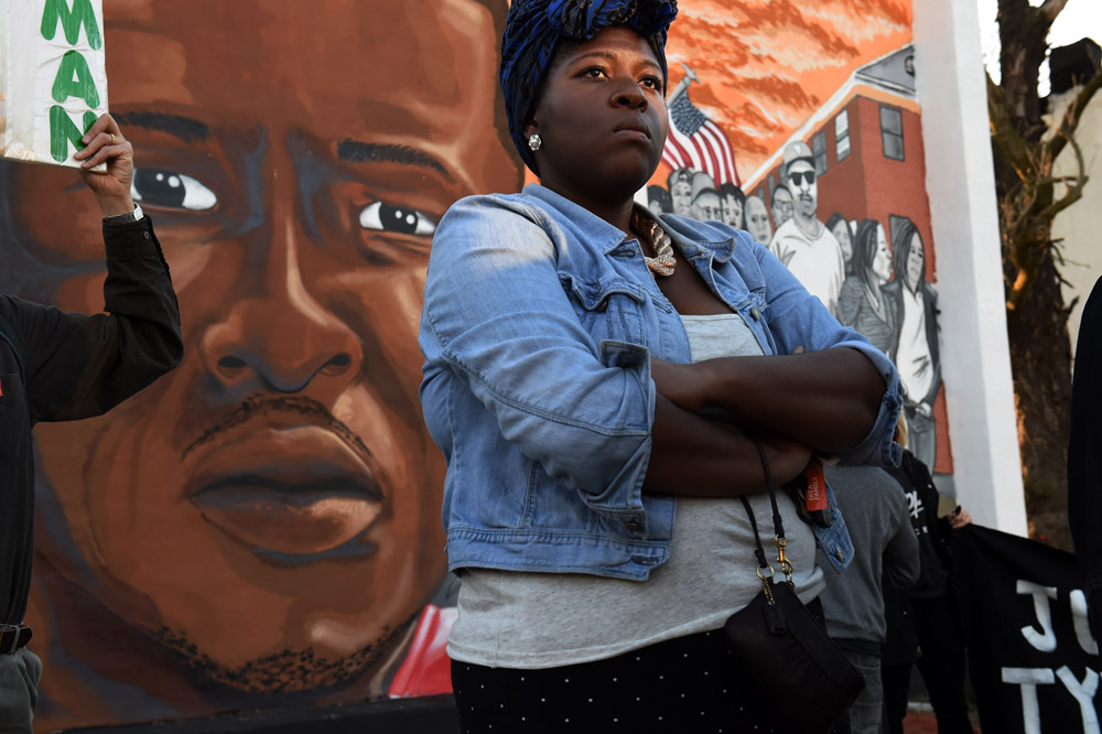 Qiara Butler, who is the cousin of Tyrone West, joins with fellow family members and others for a rally for West in front of a mural portraying Freddie Gray on Wednesday April 20, 2016 in Baltimore, MD. The city saw unrest following the death of Freddie Gray last year. (Photo by Matt McClain/ The Washington Post)