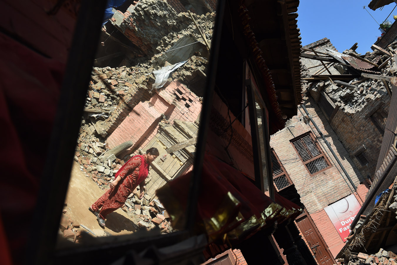 A woman is reflected in a mirror as she walks near Bhaktapur Durbar Square on Saturday May 02, 2015 in Bhaktapur, Nepal. A deadly earthquake in Nepal has killed thousands. (Photo by Matt McClain/ The Washington Post)