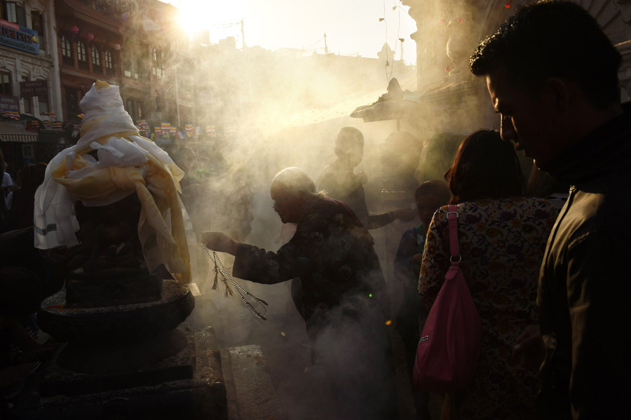 Smoke engulfs people as they celebrate Buddha Purnima which commemorates the birthday of Buddha near the Boudhanath stupa on Monday May 04, 2015 in Kathmandu, Nepal. Scores of people gathered for the festival near the historic stupa. (Photo by Matt McClain/ The Washington Post)