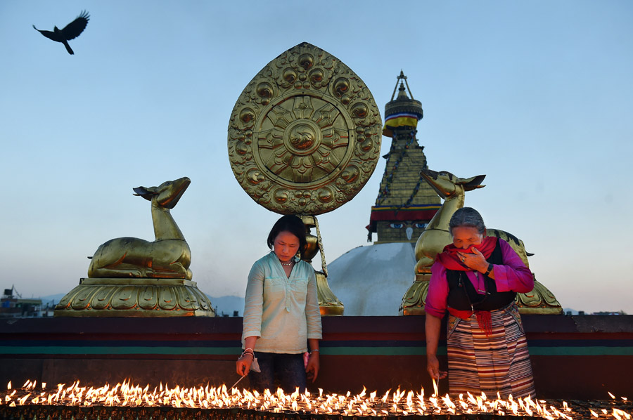 Women light candles as they celebrate Buddha Purnima which commemorates the birthday of Buddha near the Boudhanath stupa on Monday May 04, 2015 in Kathmandu, Nepal. Scores of people gathered for the festival near the historic stupa. (Photo by Matt McClain/ The Washington Post)