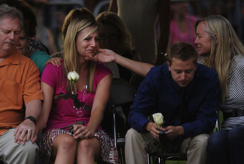 Amanda Lindren, second from left, girlfriend of shooting victim, Alexander Teves is comforted while she grieves with others closely associated with the victims of the Century Aurora 16 movie theater shooting during a community vigil at the Aurora Municipal Center on Sunday July 22, 2012 in Aurora, CO.  Teves used his body to block Lindren from the gunfire and was killed.  The event was to honor the memories of those injured and killed in the deadly shooting Friday morning at the Century Aurora 16 that left twelve dead.  (Photo by Matt McClain for The Washington Post)