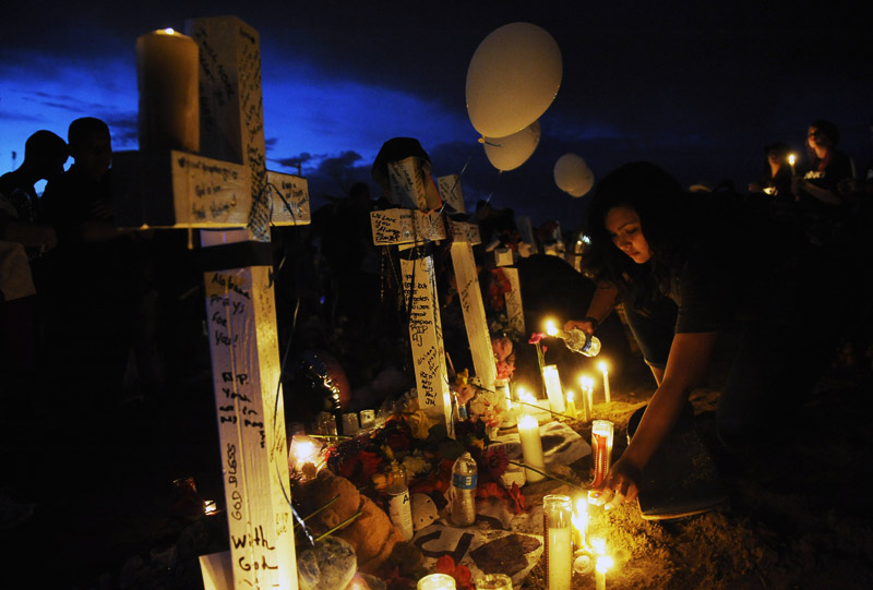 AURORA, CO - JULY 22:  Rachel Fogleman, 13, of Aurora, CO lights candles near a makeshift memorial that includes twelve crosses across the street from the Century Aurora 16 movie theater on Sunday July 22, 2012 in Aurora, CO.  The crosses represent the twelve people who were killed in a deadly shooting Friday morning at the movie theater.  (Photo by Matt McClain for The Washington Post)