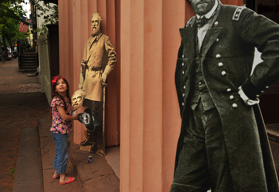Eve Spencer, 6, holds masks of Robert E. Lee and Ulysses S. Grant outside the Athenaeum during the Civil War Flash Mob that encouraged people to dress in period Civil War dress on Sunday April 28, 2013 in Alexandria, VA.  (Photo by Matt McClain/ The Washington Post)