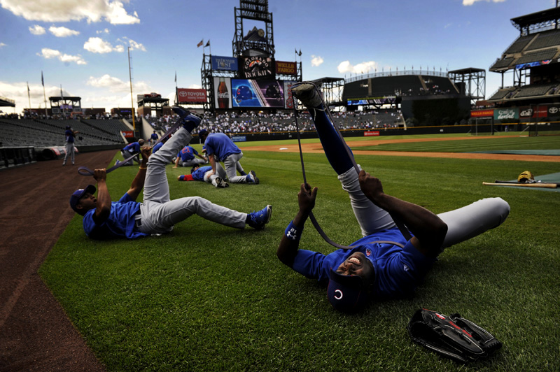 Chicago Cubs' outfielder, Alfonso Soriano, right, grimaces as he stretches with teammates prior to a baseball game against the Colorado Rockies at Coors Field in Denver, Colo. on Saturday, July 31, 2010.  (AP Photo/ Matt McClain)