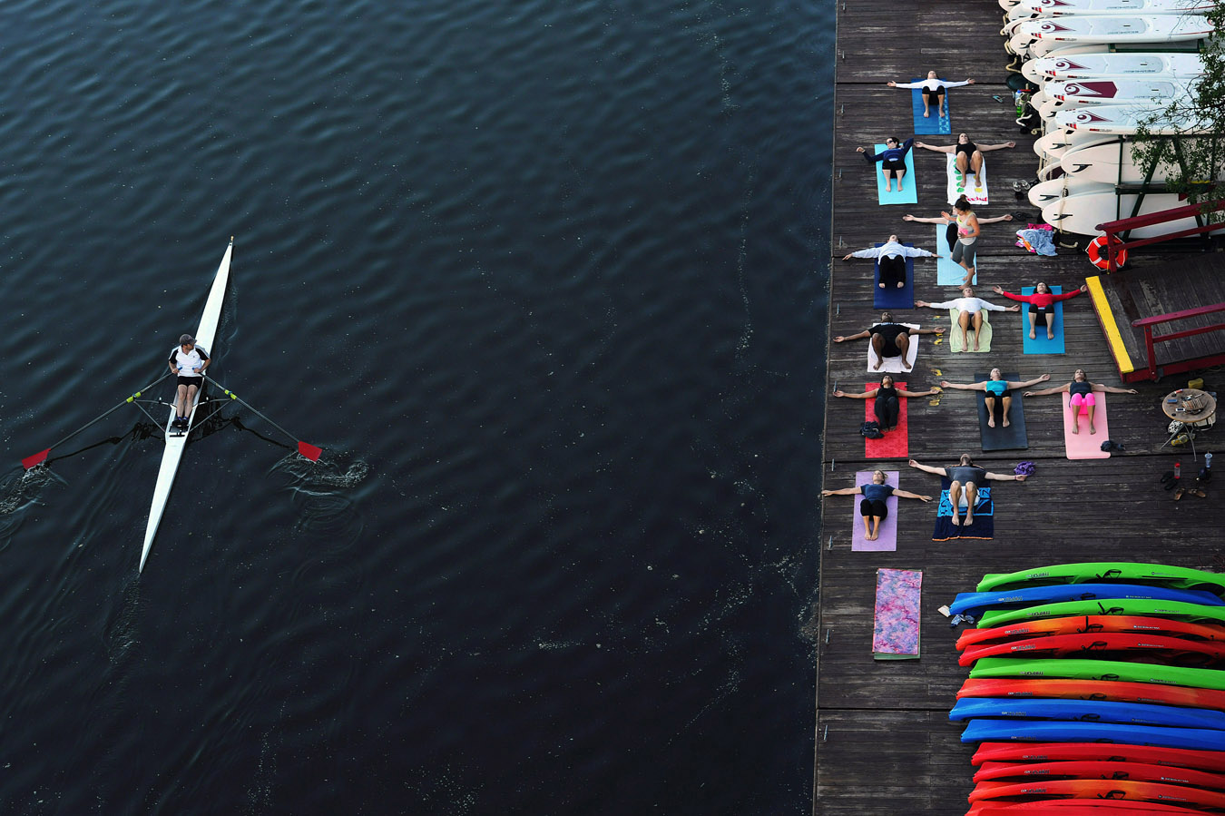 A rower glides by as people take part in {quote}Yoga on the Docks{quote} at Key Bridge Boathouse on Saturday June 07, 2014 in Washington, DC.  The morning yoga session will run on Saturdays for the next several months.  (Photo by Matt McClain/ The Washington Post)
