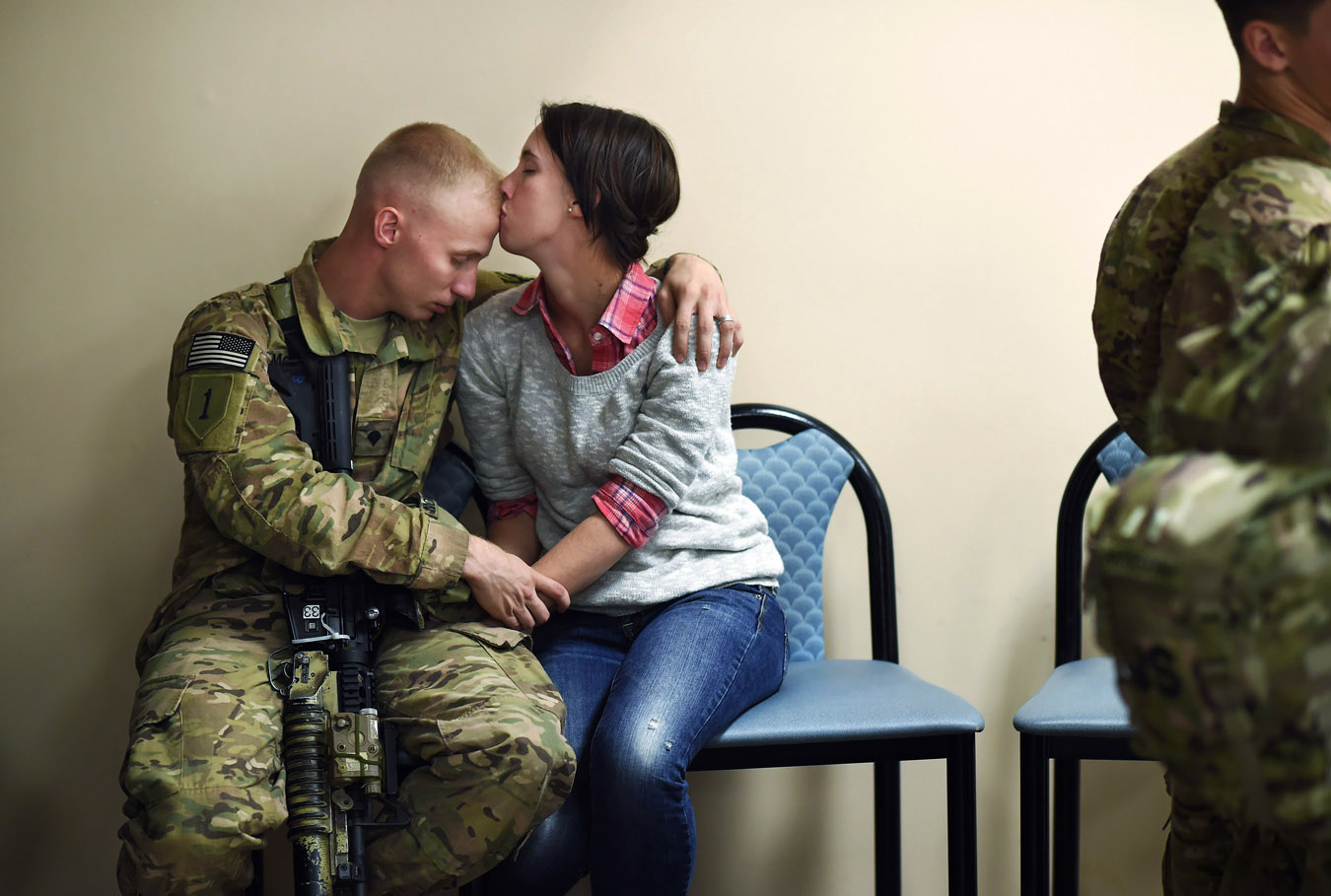 SPC Caleb McKinnon embraces his wife, Savannah McKinnon as he and others prepare to be deployed to Afghanistan from Fort Campbell on Sunday November 09, 2014 in Fort Campbell, KY.  (Photo by Matt McClain/ The Washington Post)