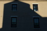 A shadow of a building is cast on another building as a man works on a window on Thursday February 21, 2013 in Alexandria, VA.  (Photo by Matt McClain for The Washington Post)