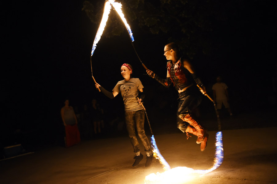 Karly Bellingham, left center, and Laura Durbin, right, practice with flaming jump ropes as they and other members of Revolutionary Motion work on a fire routine on Wednesday August 12, 2015 in Alexandria, VA. The group will be performing at the upcoming Burning Man festival in Nevada. (Photo by Matt McClain/The Washington Post)