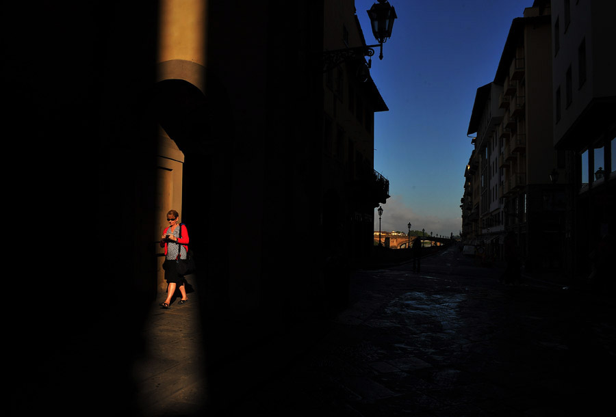 A pedestrian walks through a sliver of morning light on Saturday May 18, 2013 in Florence, Italy.  Florence is home to many Renaissance master works, including Michelangelo's David.  (Photo by Matt McClain/ The Washington Post)