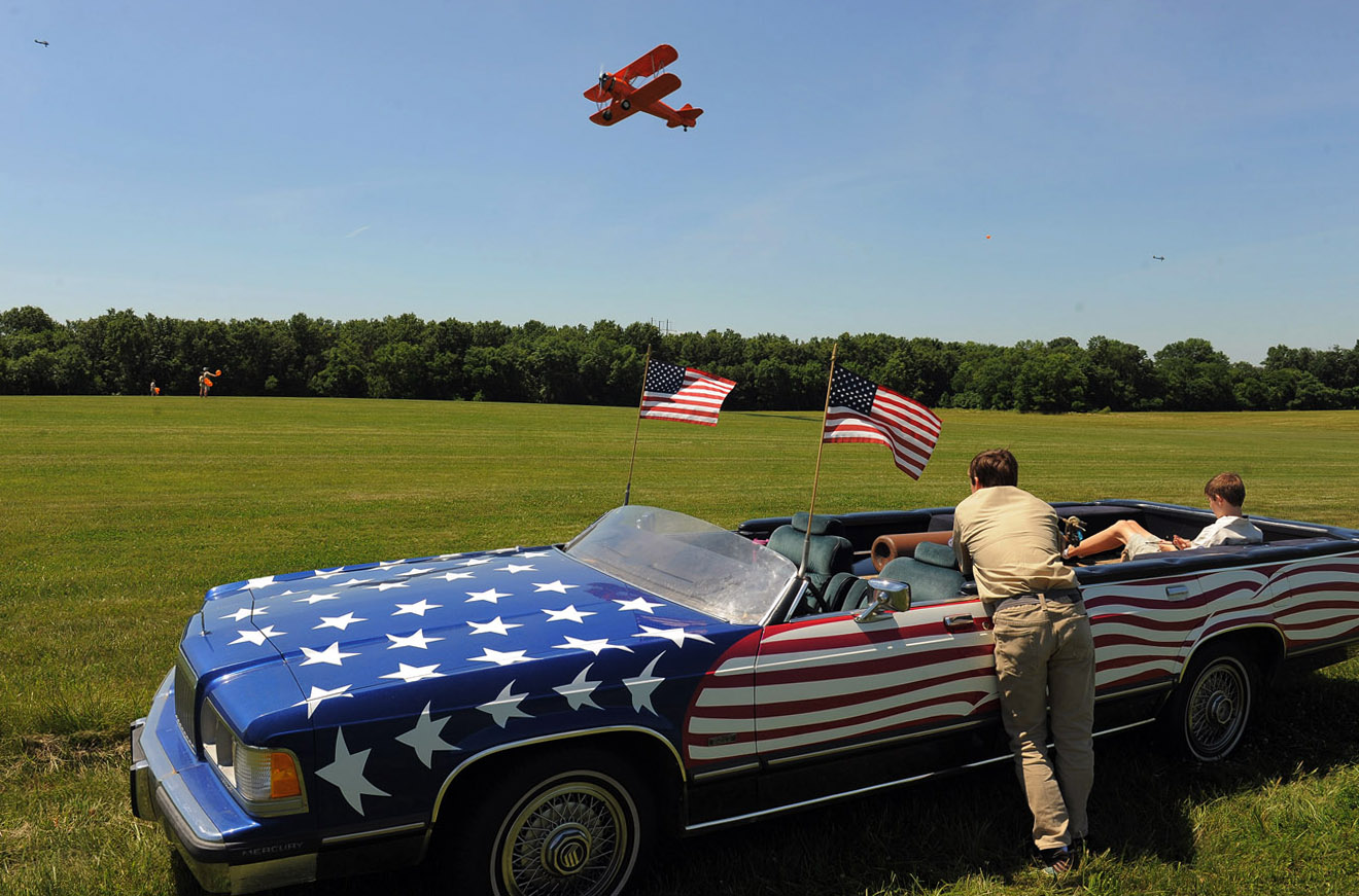 Volunteers with the show, Peter Deer, right center, and Lance King, right, watch flying displays during the Flying Circus Airshow on Sunday June 15, 2014 in Bealeton, VA.  (Photo by Matt McClain/ The Washington Post)