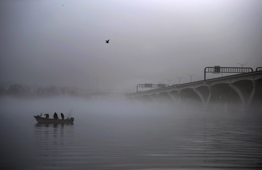 Shrouded in fog, people fish near the Woodrow Wilson Memorial Bridge on the Potomac River on Saturday January 12, 2013 in Alexandria, VA.  (Photo by Matt McClain for The Washington Post)