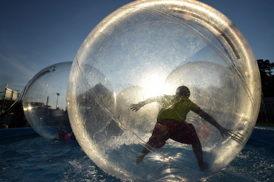 Brian Ortega, 10, tries to stand up in an inflated globe that was part of the Jersey Shore attraction at the Arlington County Fair on Wednesday August 05, 2015 in Arlington, VA. The fair, which runs through August 09, 2015 is located on the grounds of the Thomas Jefferson Community and Fitness Center.  (Photo by Matt McClain/The Washington Post)